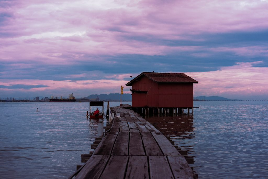 A stilt wooden house with a wooden path leading to it with Penang's horizon is behind.