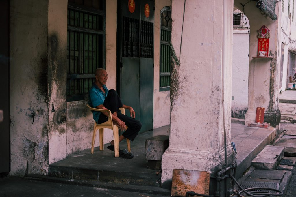 A man sitting outside his house, observing life on the street