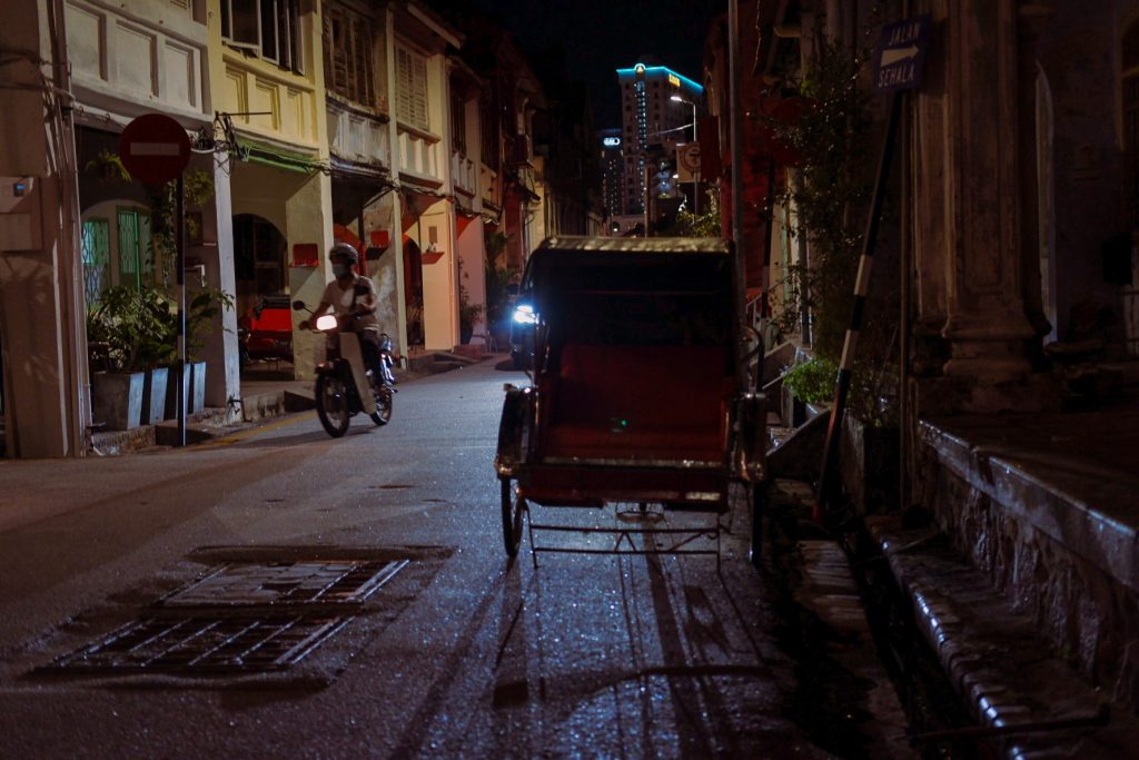 A trishaw by the roadside at night with a passing car throwing light on it