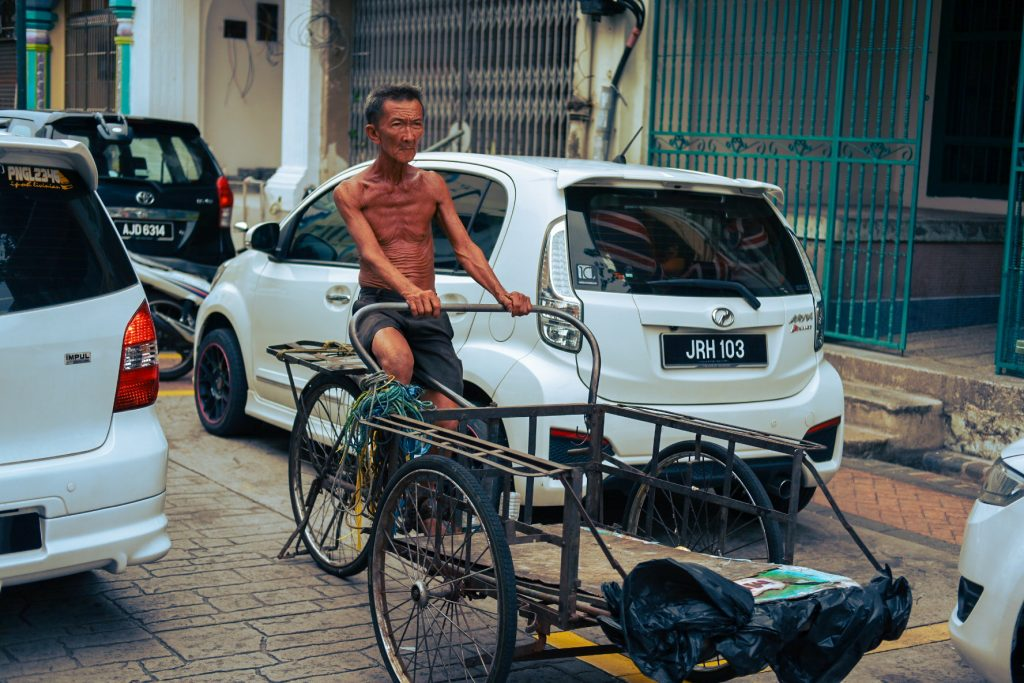 Skinny, tanned, barechested man riding an empty cart bicycle surrounded by cars.