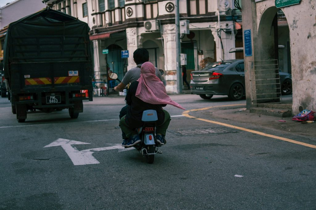 A man and a woman wearing a scarf on a motorbike. The scarf is moving with the air.