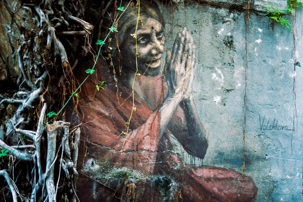 Mural of a woman with hands in prayer