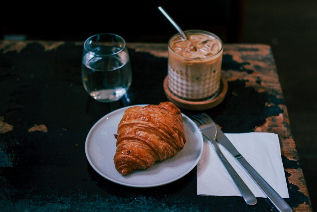 A croissant and ice cafe latte laid on a wooden table