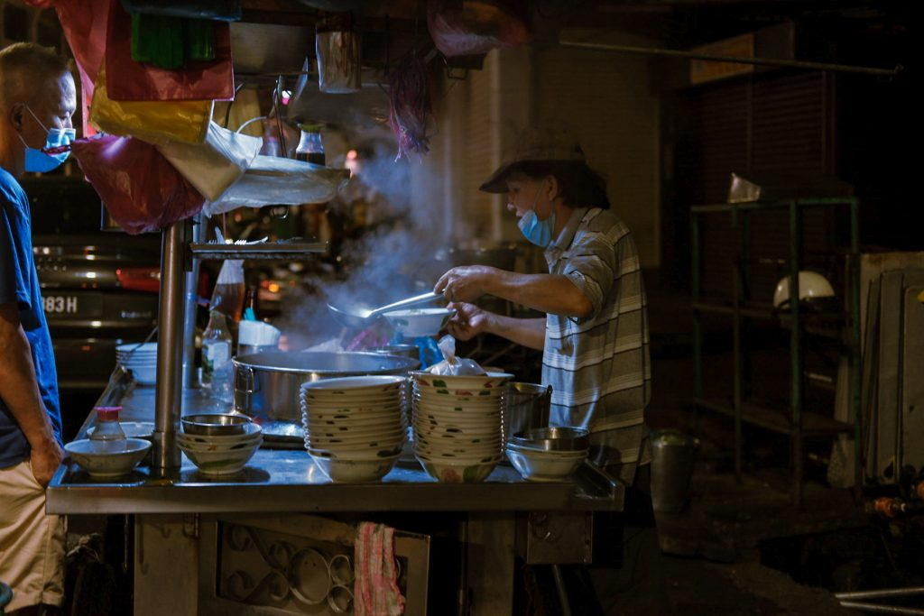 A hawker serving soup to a customer at night. Smoke is coming from his pots