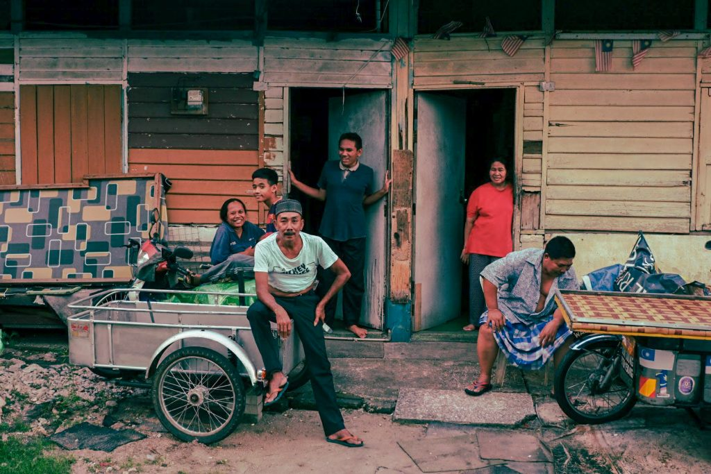 Family chilling in front of a traditional house in a traditional village