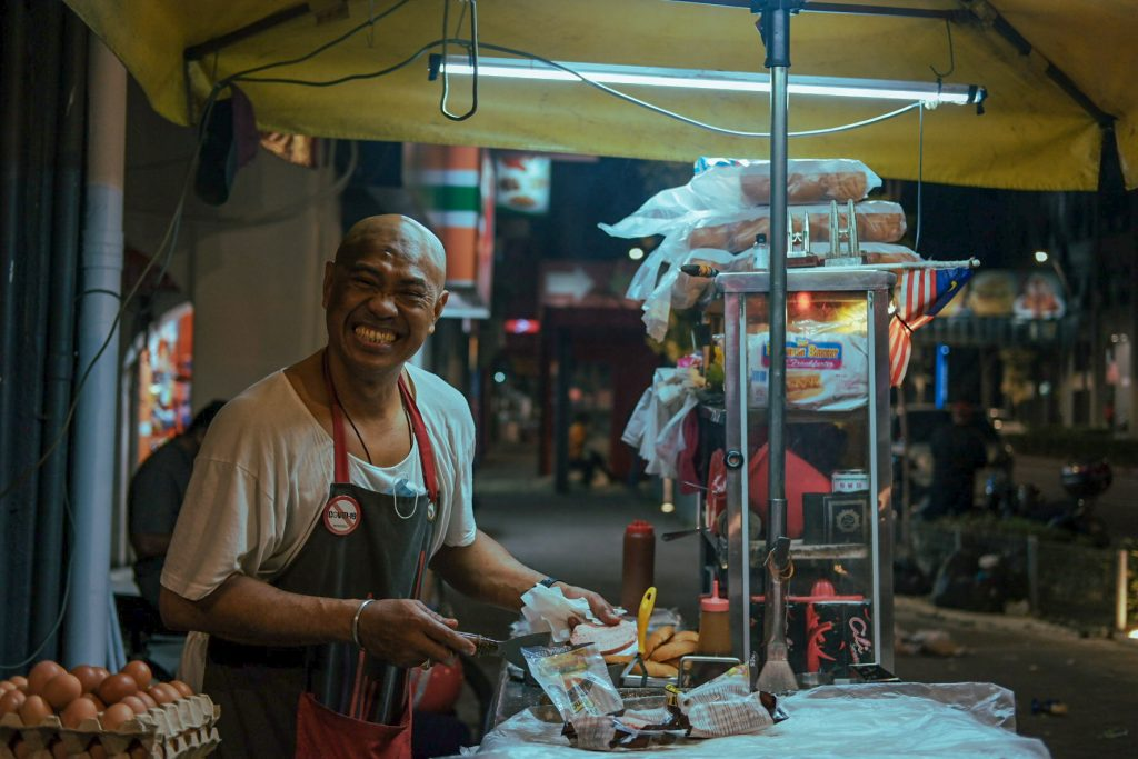 AA man smiling from ear to ear selling food in his stall by night