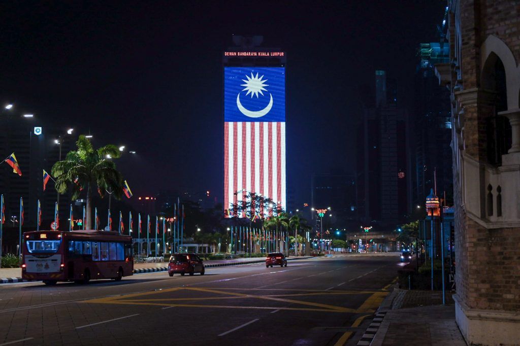 Flag of Malaysia hanging down from a building at night with cars on the street