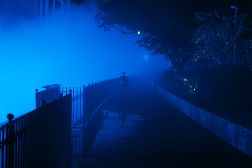 A man is emerging from blue steam released by the river of life in KL by night.