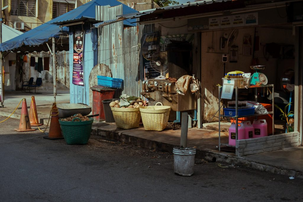 Baskets and other stuff laid before a shop in a village lit by sunset