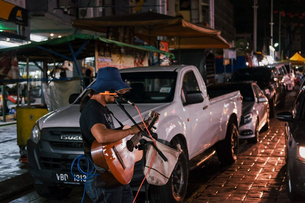 Busker tuning his guitar in a street by night
