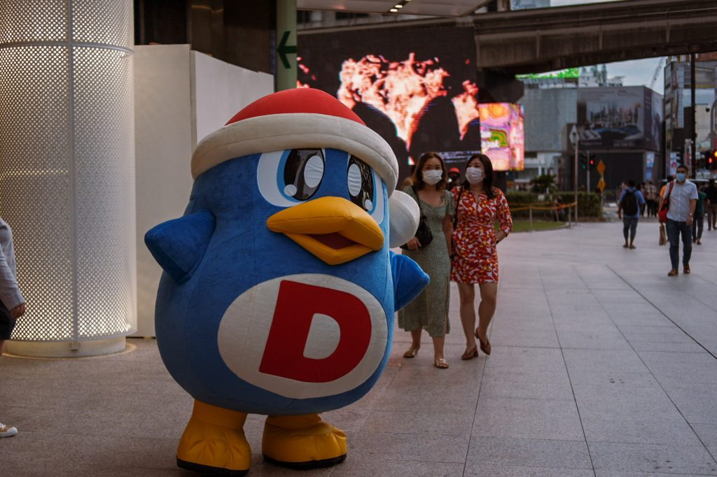 Silly blue mascot inviting people to a restaurant