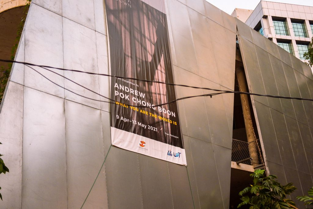 Huhe banner on a wall of building advertising an exhibition of an artist