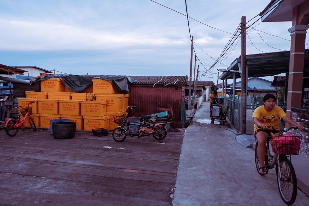 A woman wearing orange cycling near orange storage containers