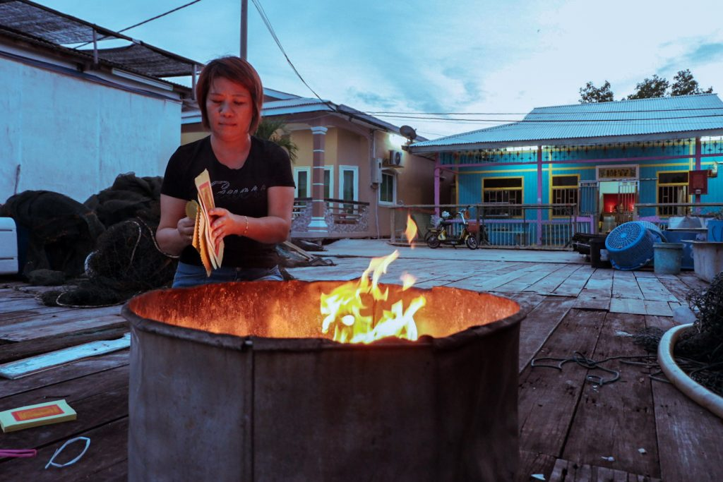 Peggy burning Chinese paper money in front of her house.