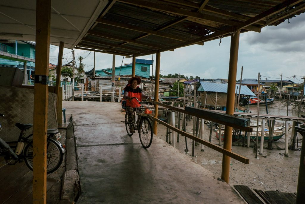A woman on a bicycle riding under a roof