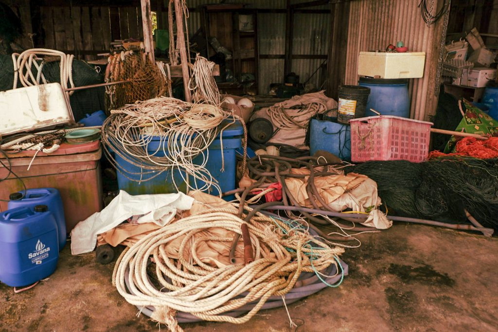 A porch outside a house cluttered with the ropes and other fishing equipment