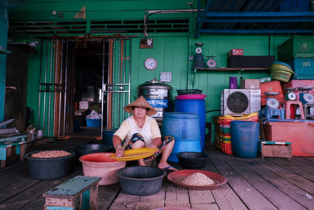 A woman sitting on a large porch in front of the house sorting fish produce