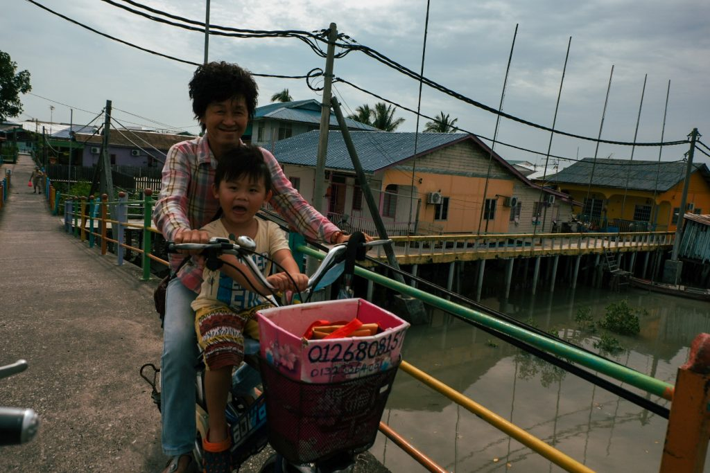 Grandma with her grandson on a bicycle with the son being excited about my taking a photo