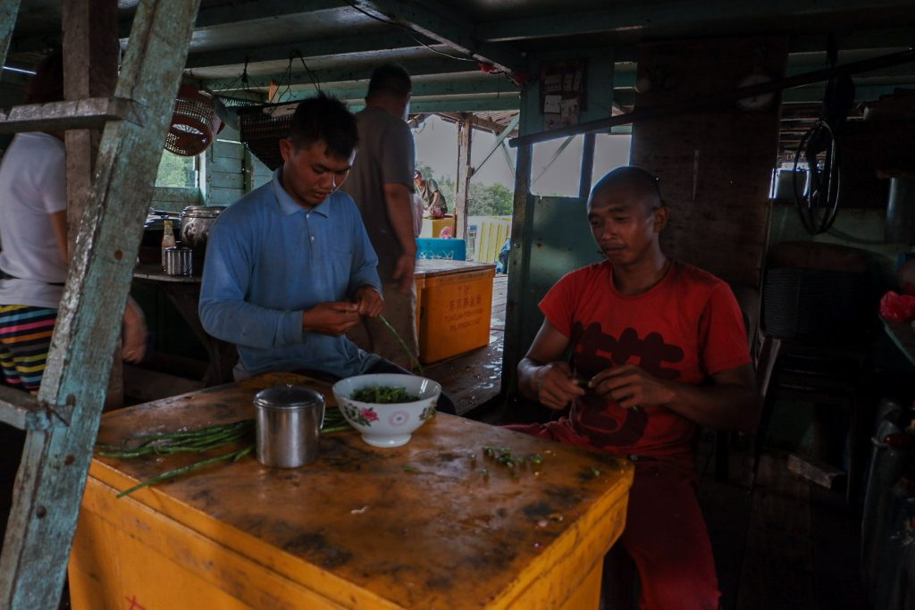 Two men are cutting vegetables for their dinner