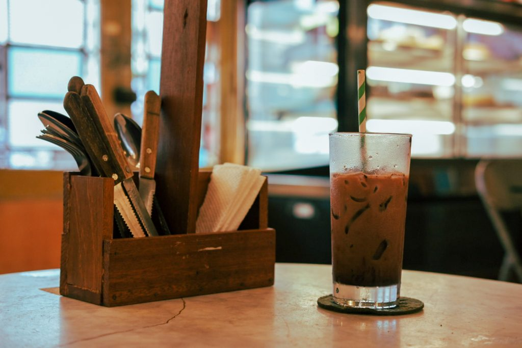 Ica mocha on a table with a wooden cutlery care next to it