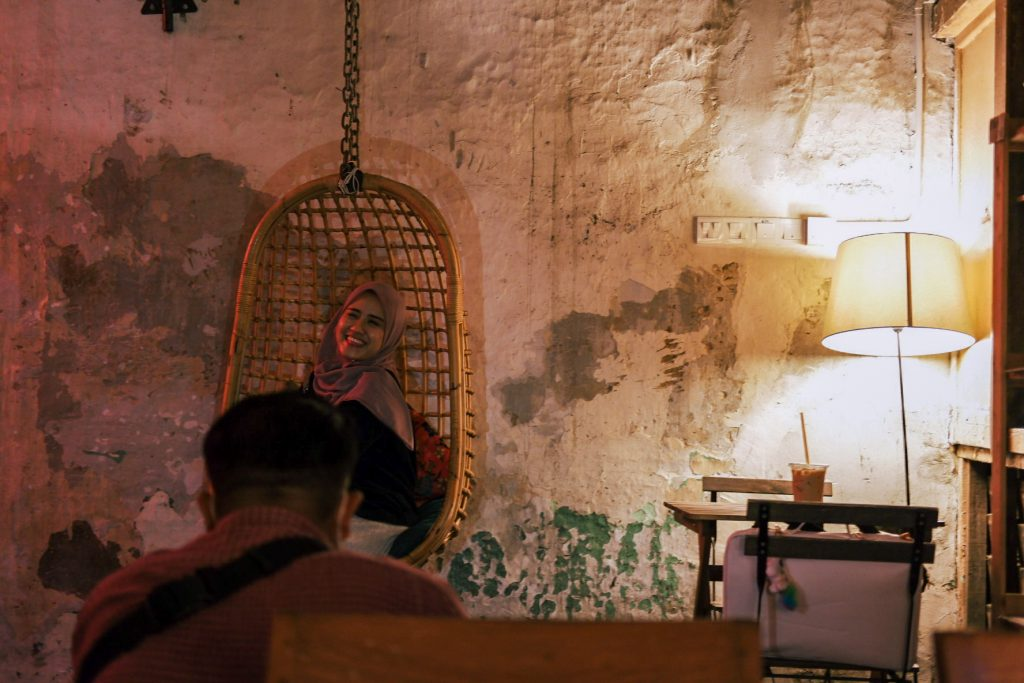 A woman in a rattan chair hung from the ceiling with a friend taking a shot of her.