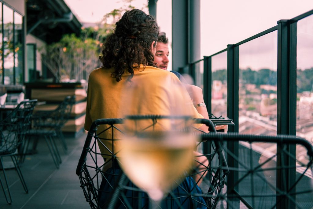 A glass of wine in blur with a man and a woman sitting at a table in the background