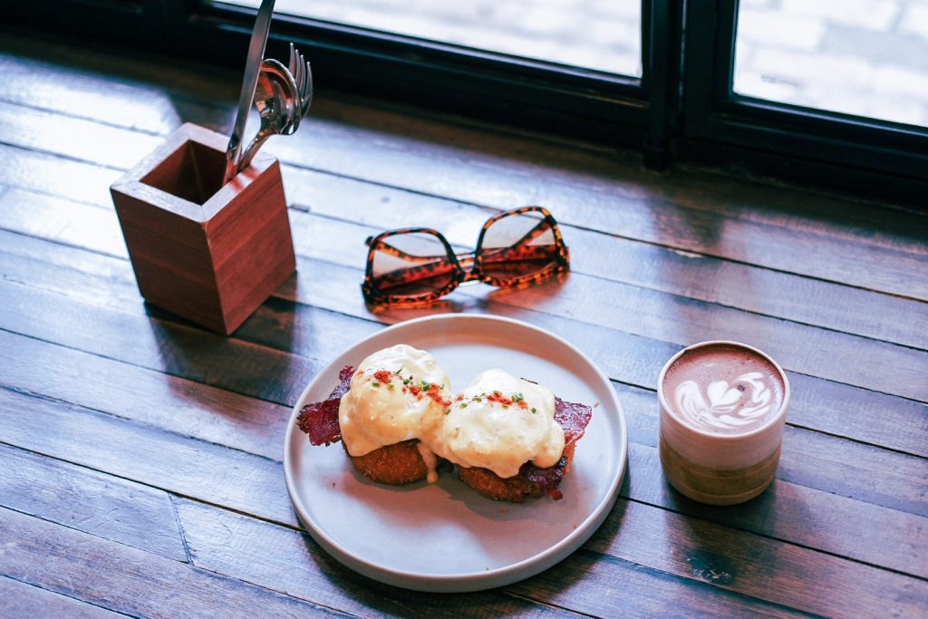 Coffee cup, egg benedit, sun glasses show from above on a table