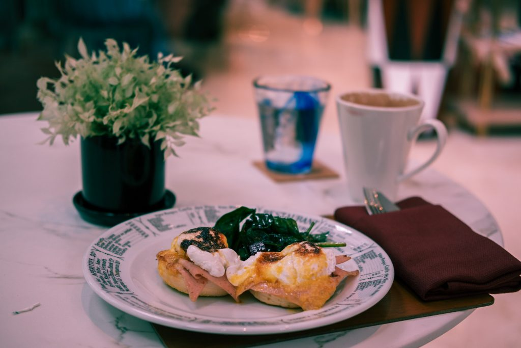 Egg benedict in focus and a cup of coffee in the background