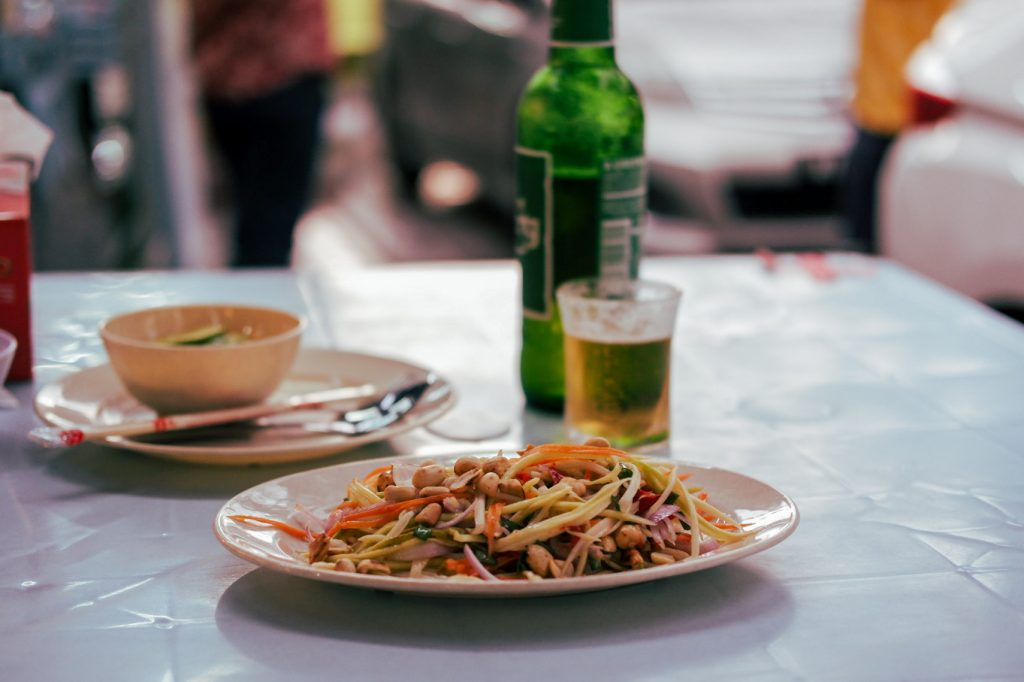 Mango salad in focus with a beer bottle in blur