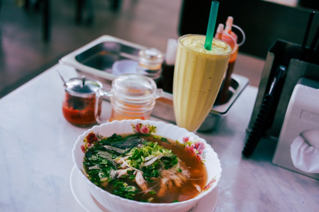 Pho and an avocado smoothie on a table