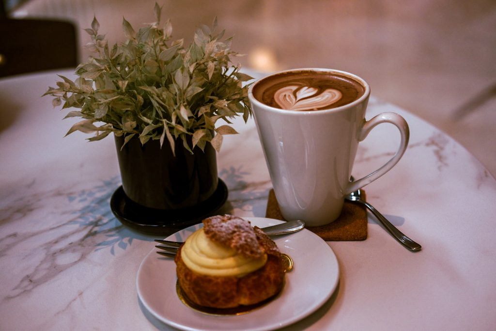 Coffee cup, cream puf and a flower on a table