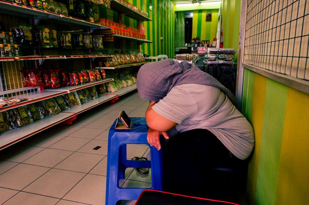 A female shop seller sleeping inside a shop