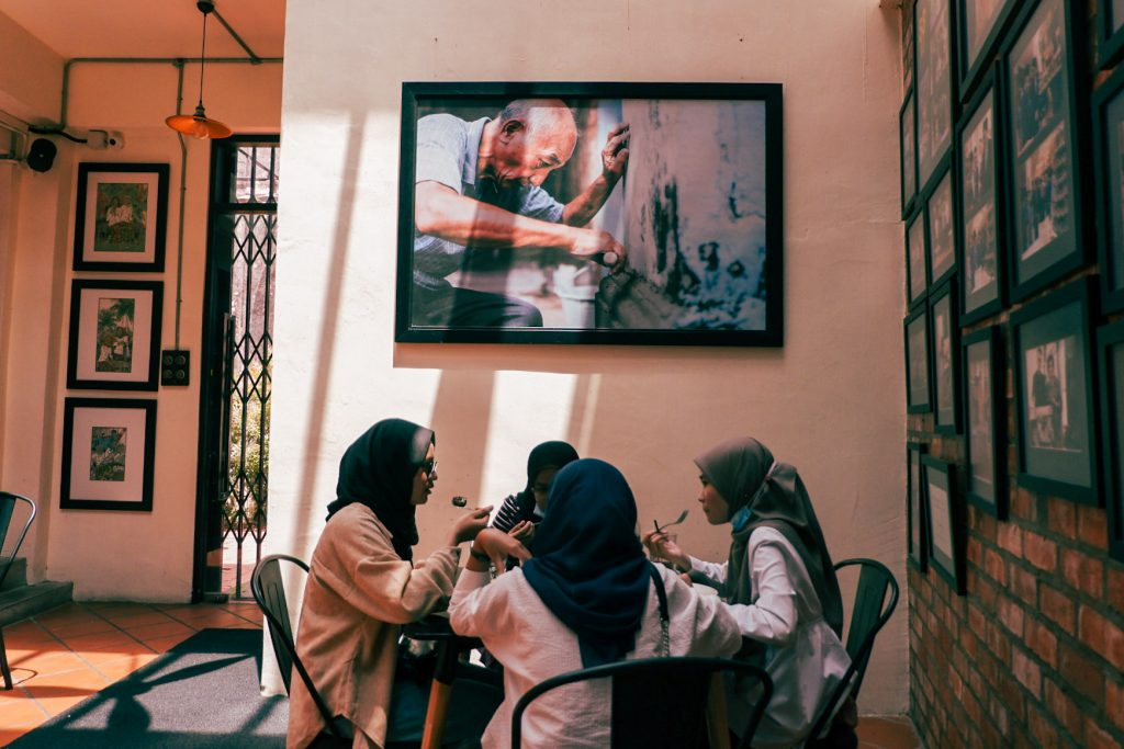 Young Muslim women at a table in a cafe having a chat