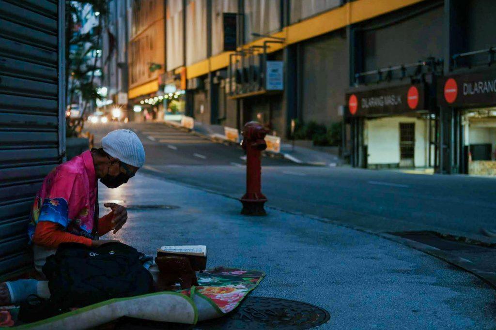 A homeless man reading Koran in the street by night