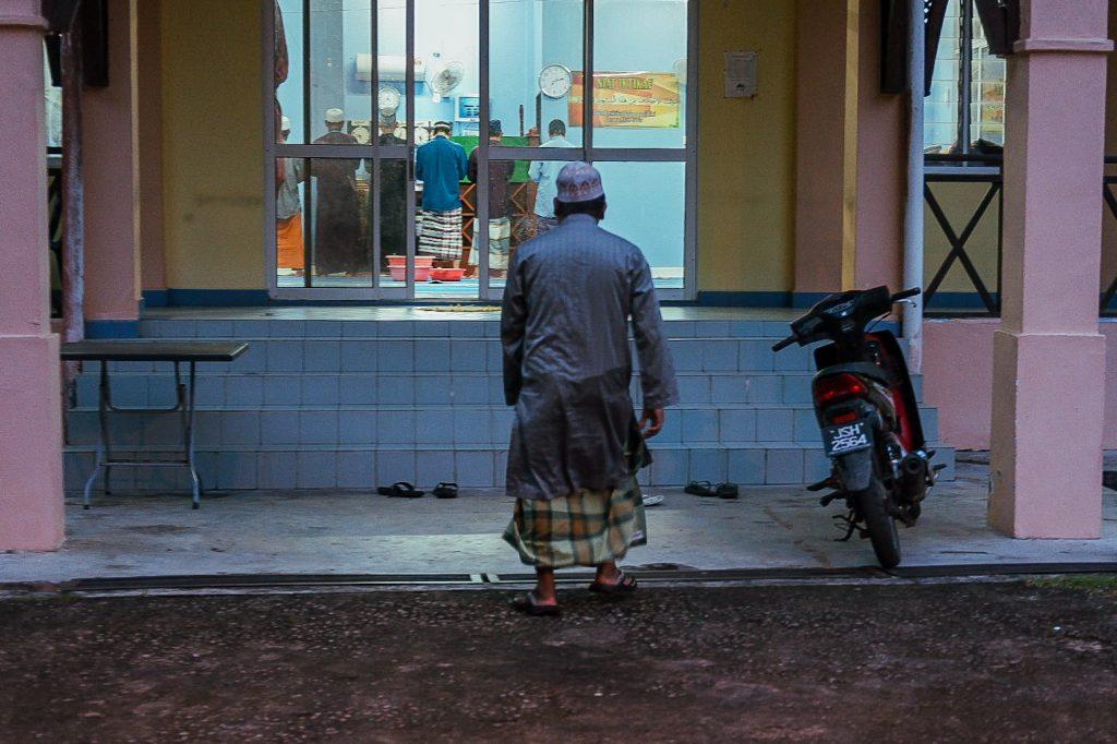 A man is walking towards a tiny mosque for an evening prayer