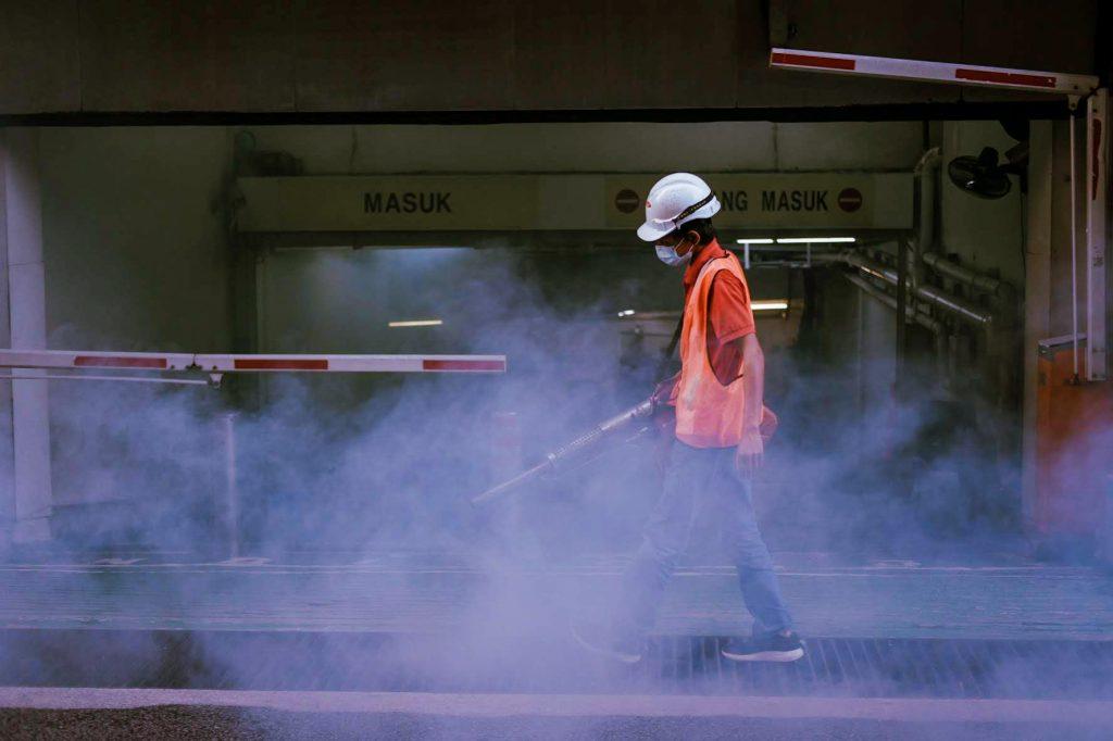 A man waering an orange west fogging in the streets