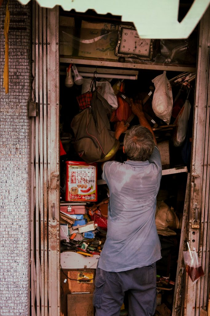 A man tries to squeeze some last items into a tiny, crammed shop before closing