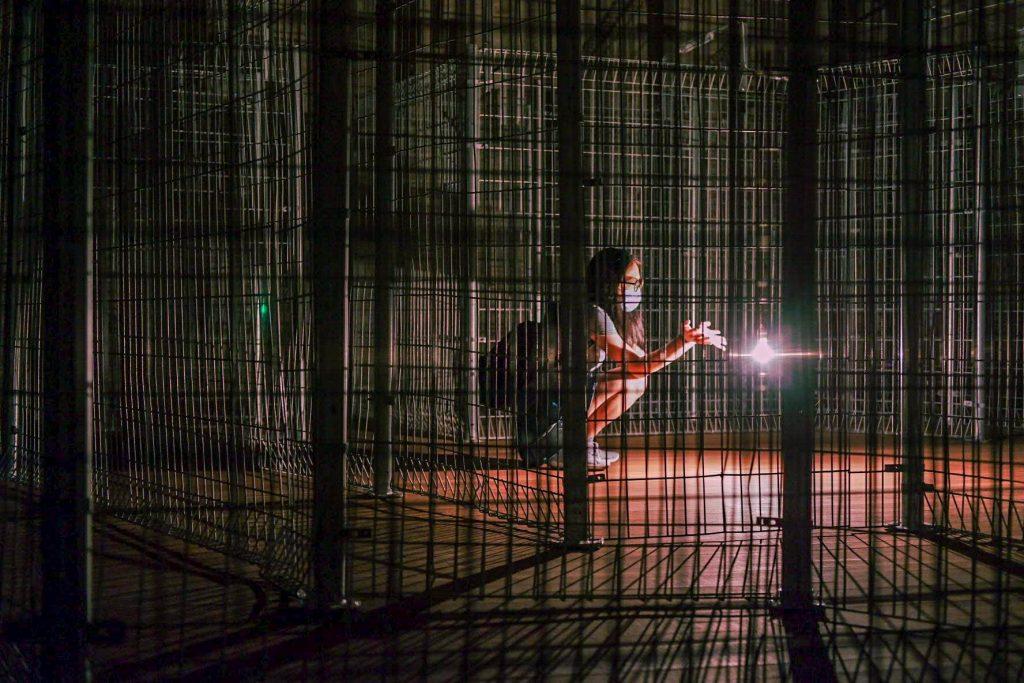 A woman in an installation reminding cage touching a bulb in the middle