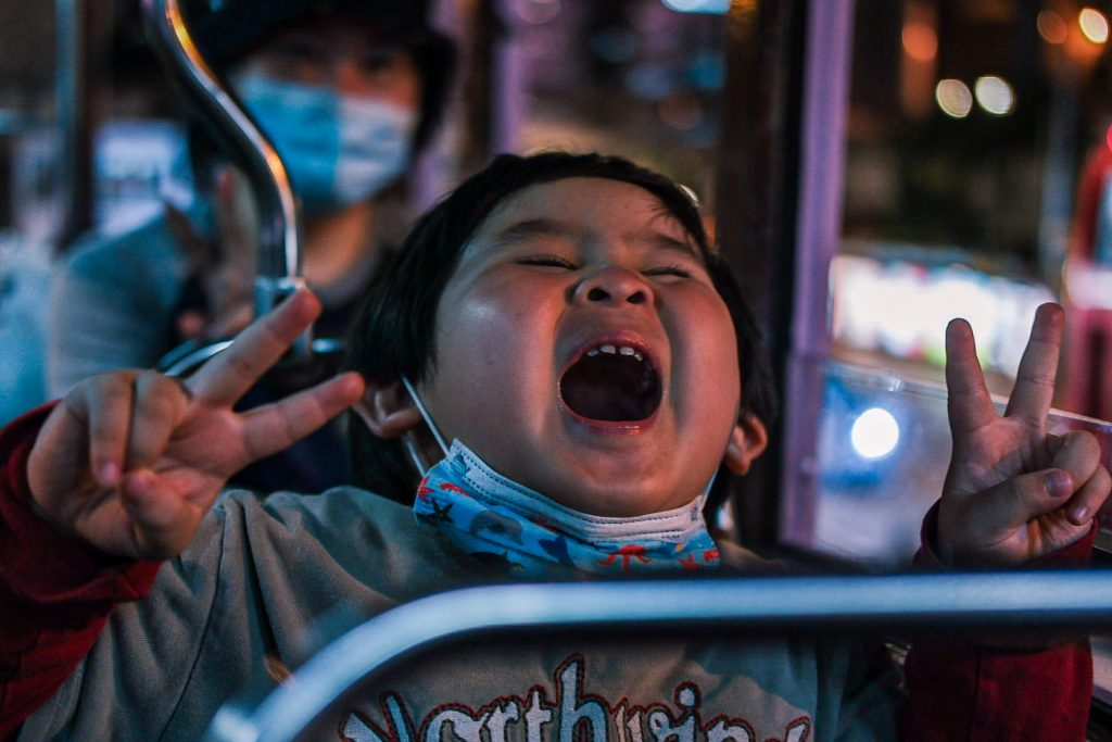 A boy on a tram seat poses for me with mouth open and fingers in the victory sign